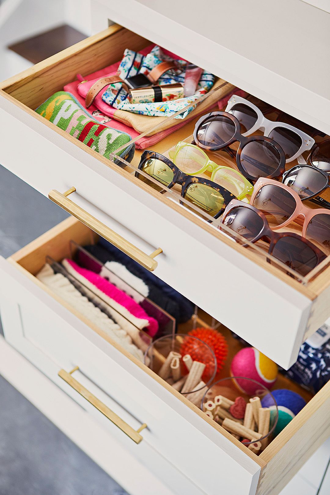 organized drawers filled with sunglasses, scarves, dog balls, dog treats