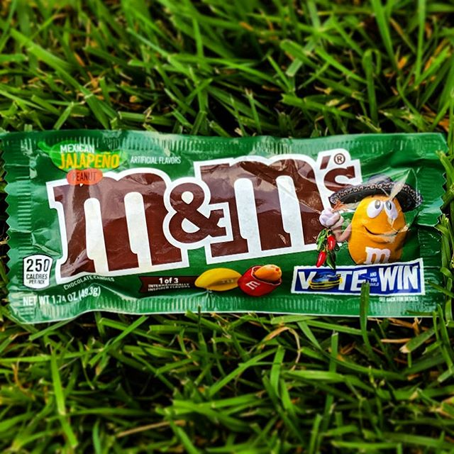 Bag of Mexican Jalapeno M and Ms in grass