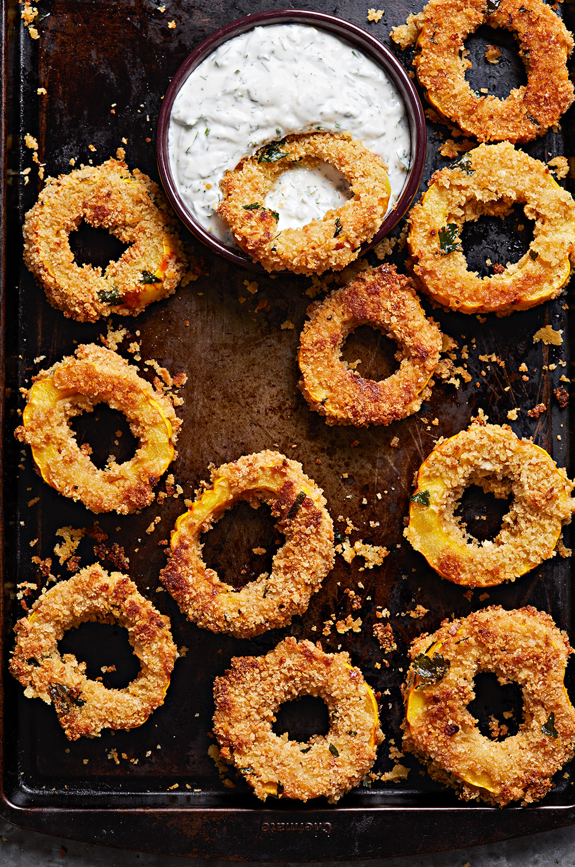 Crispy Delicata Rings with Herbed Buttermilk Dip on cookie sheet