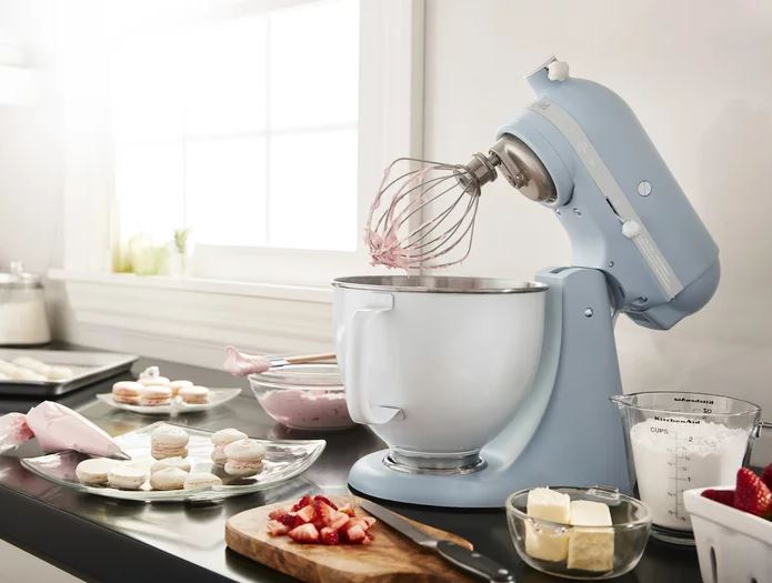 Blue KitchenAid mixing frosting for macaron cookies