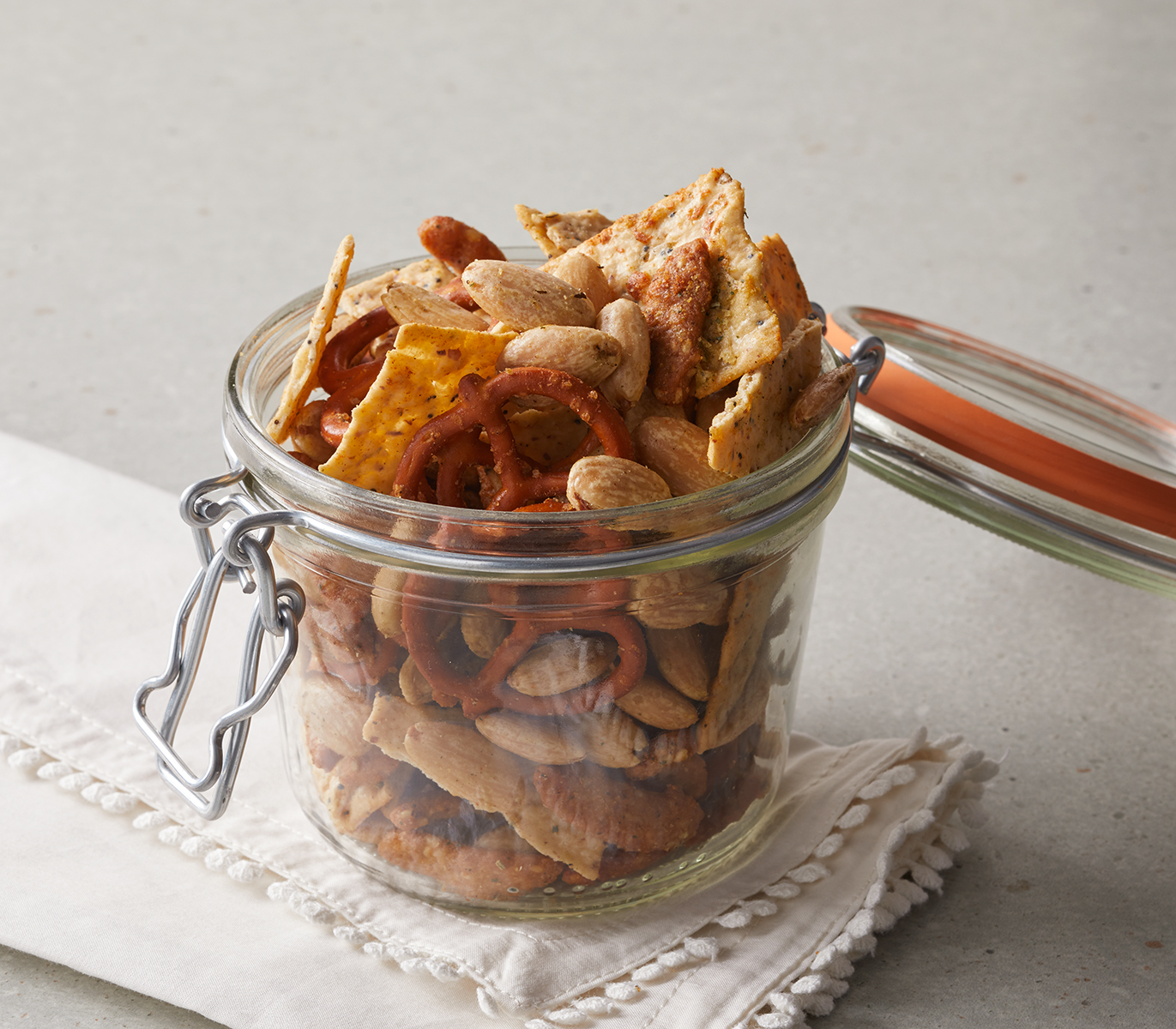 glass jar with attached lid full of snack mix