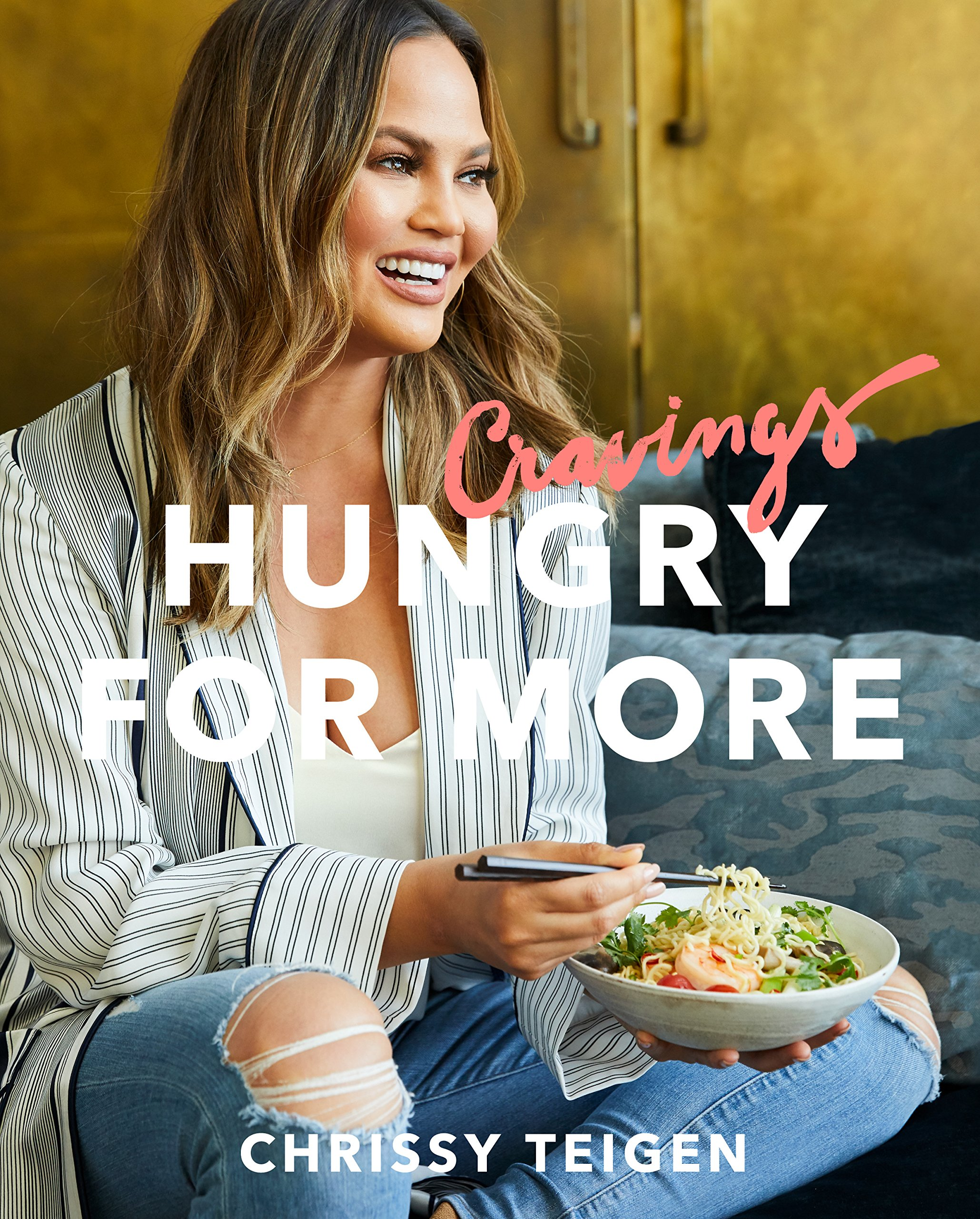Cravings: Hungry for More cookbook with Chrissy Teigen on the cover eating noodles