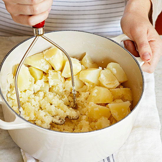 Mashing potatoes with a hand potato masher in a white saucepan