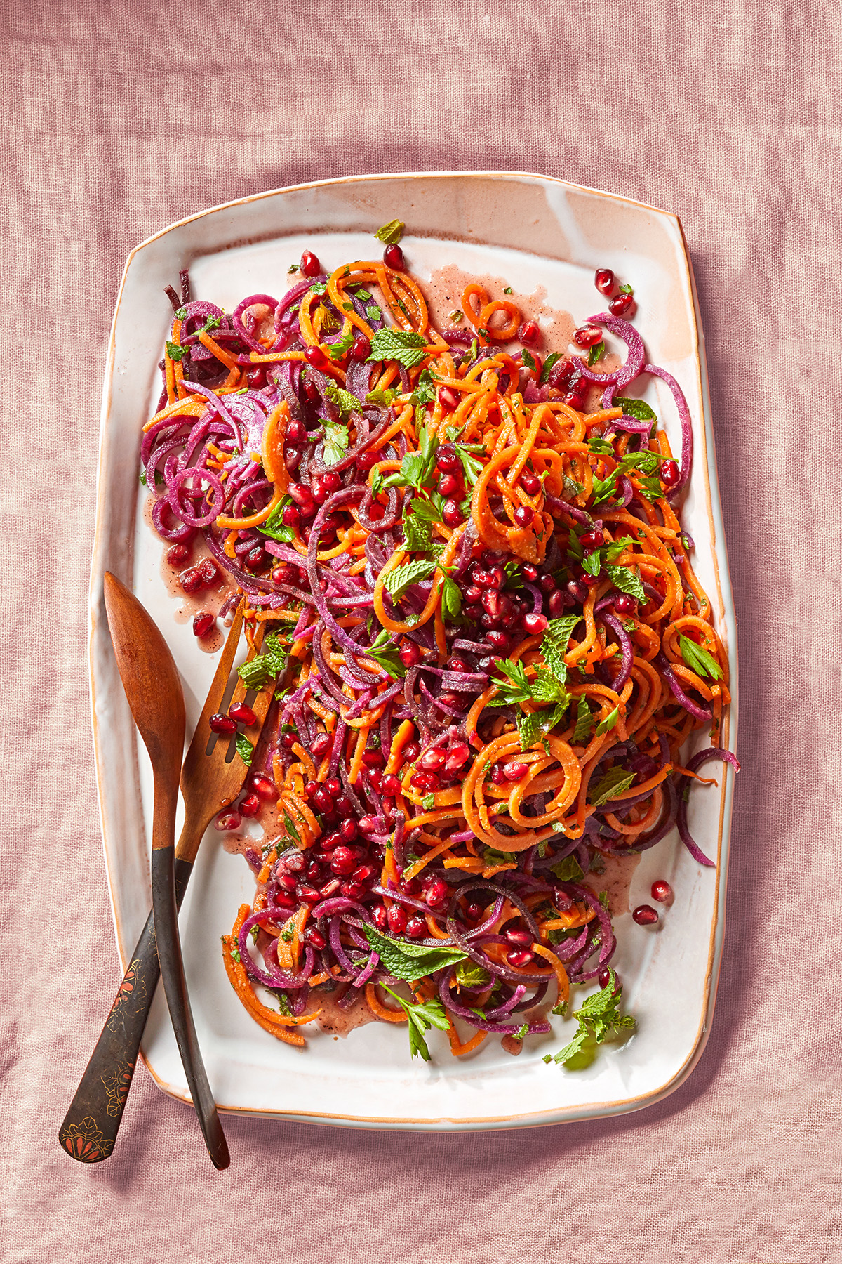 Bowl of spiralized sweet potatoes and pomegranates for Pomegranate-Glazed Sweet Potatoes