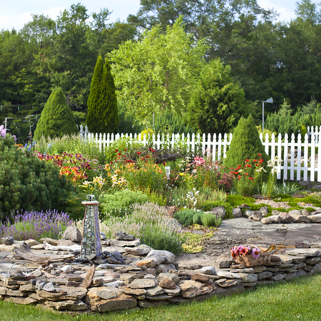 stacked stone and white picket fence in garden