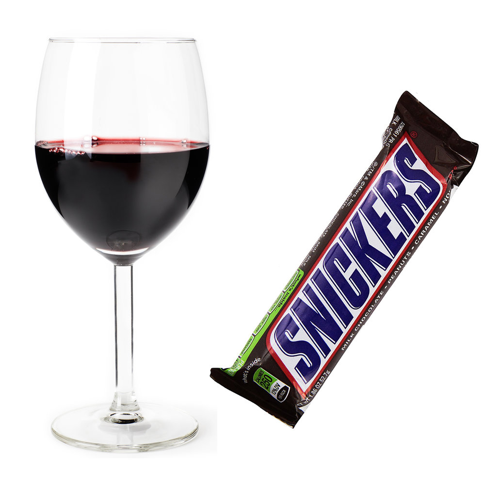 Glass of red wine and snickers bar in wrapper
