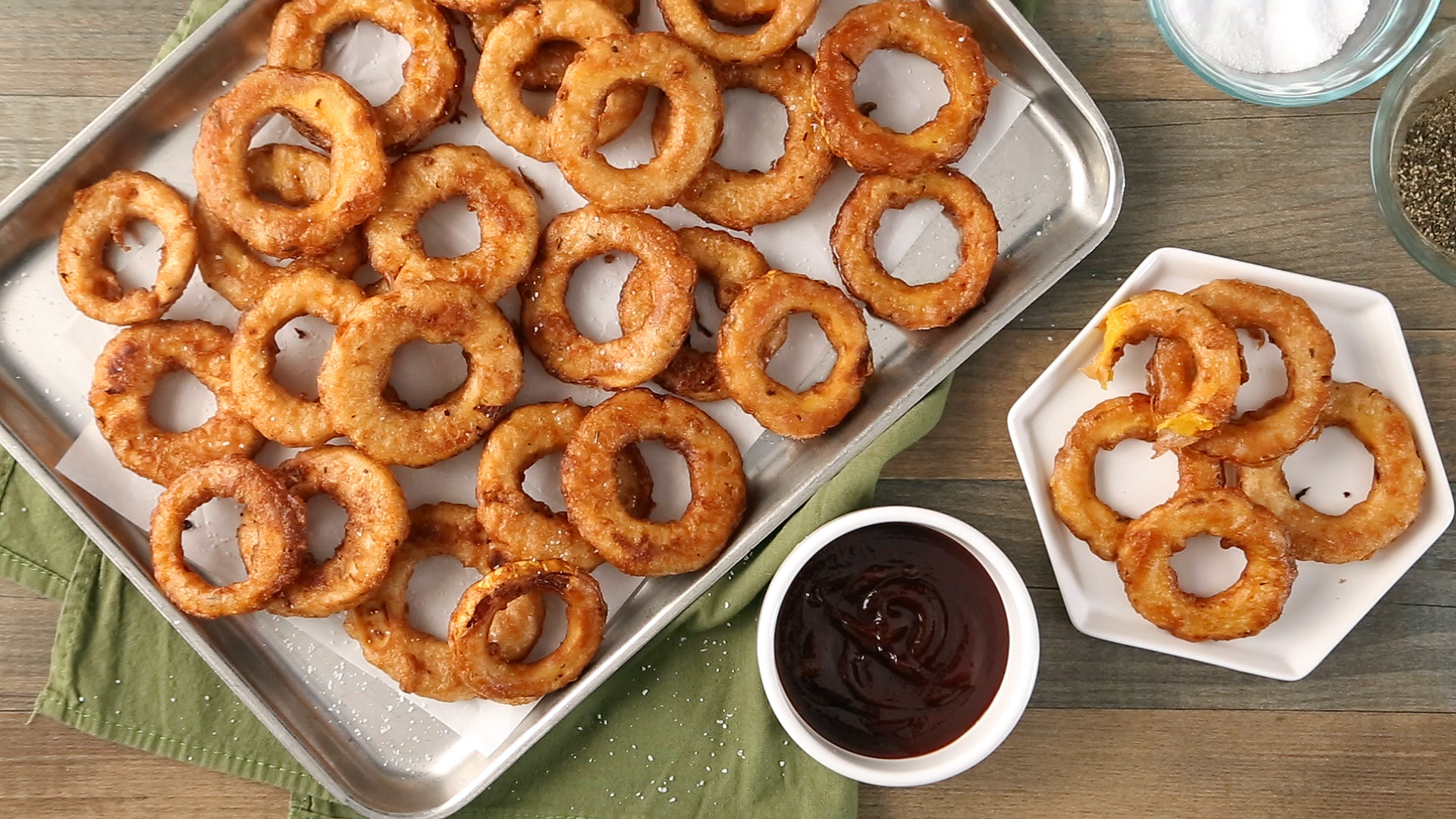 fried squash rings on parchment lined baking pan