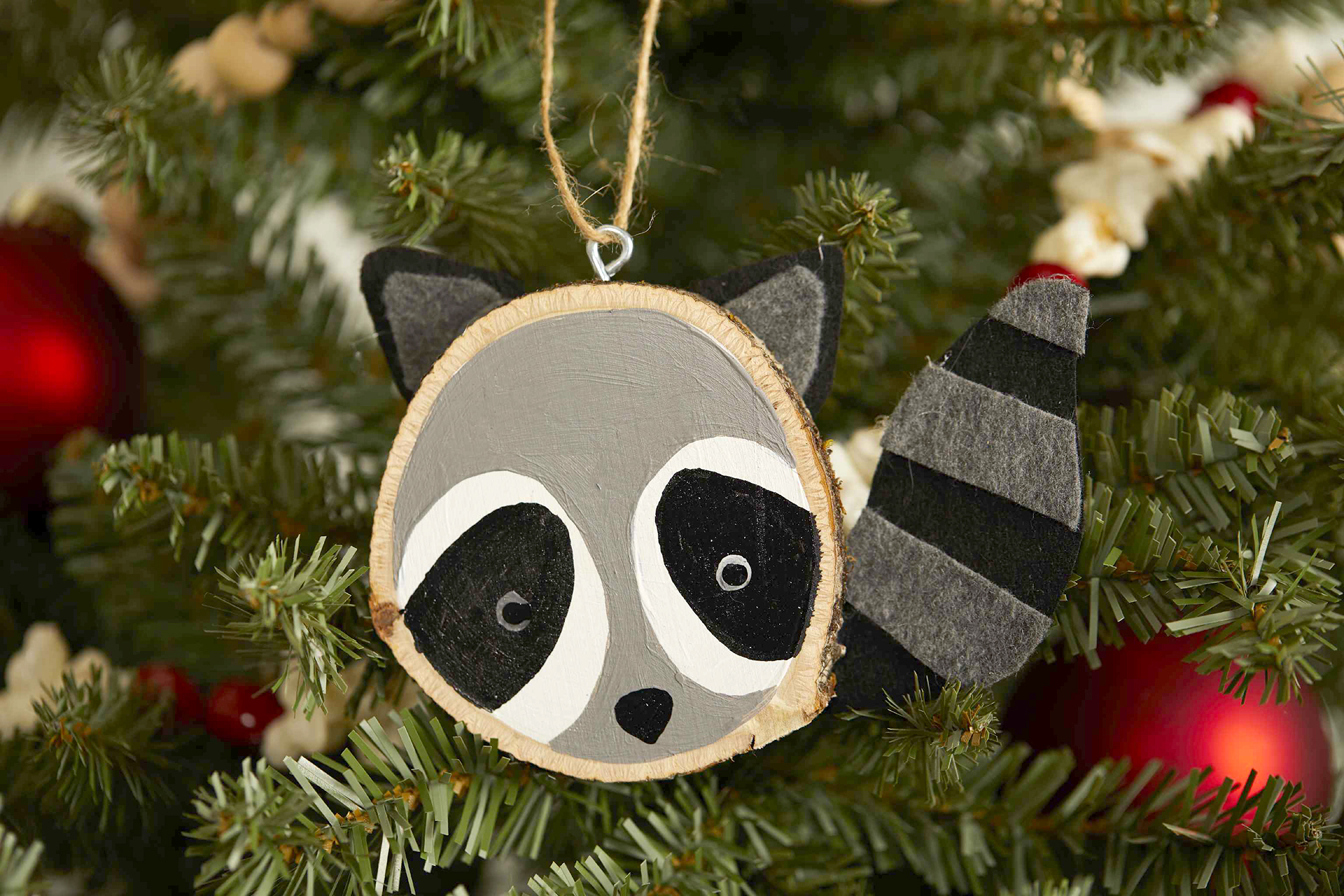 wood slice painted raccoon ornament with felt
