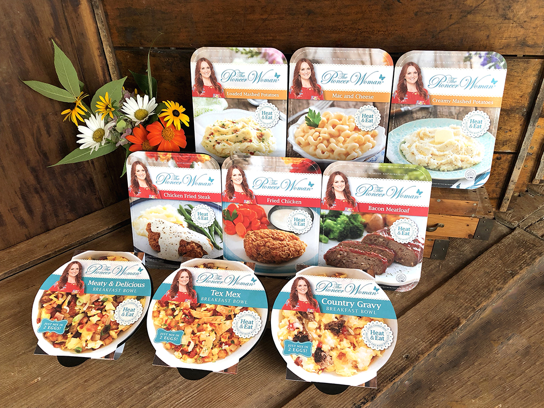 All 10 packages of the Pioneer Woman grocery line sitting on a rustic wooden surface