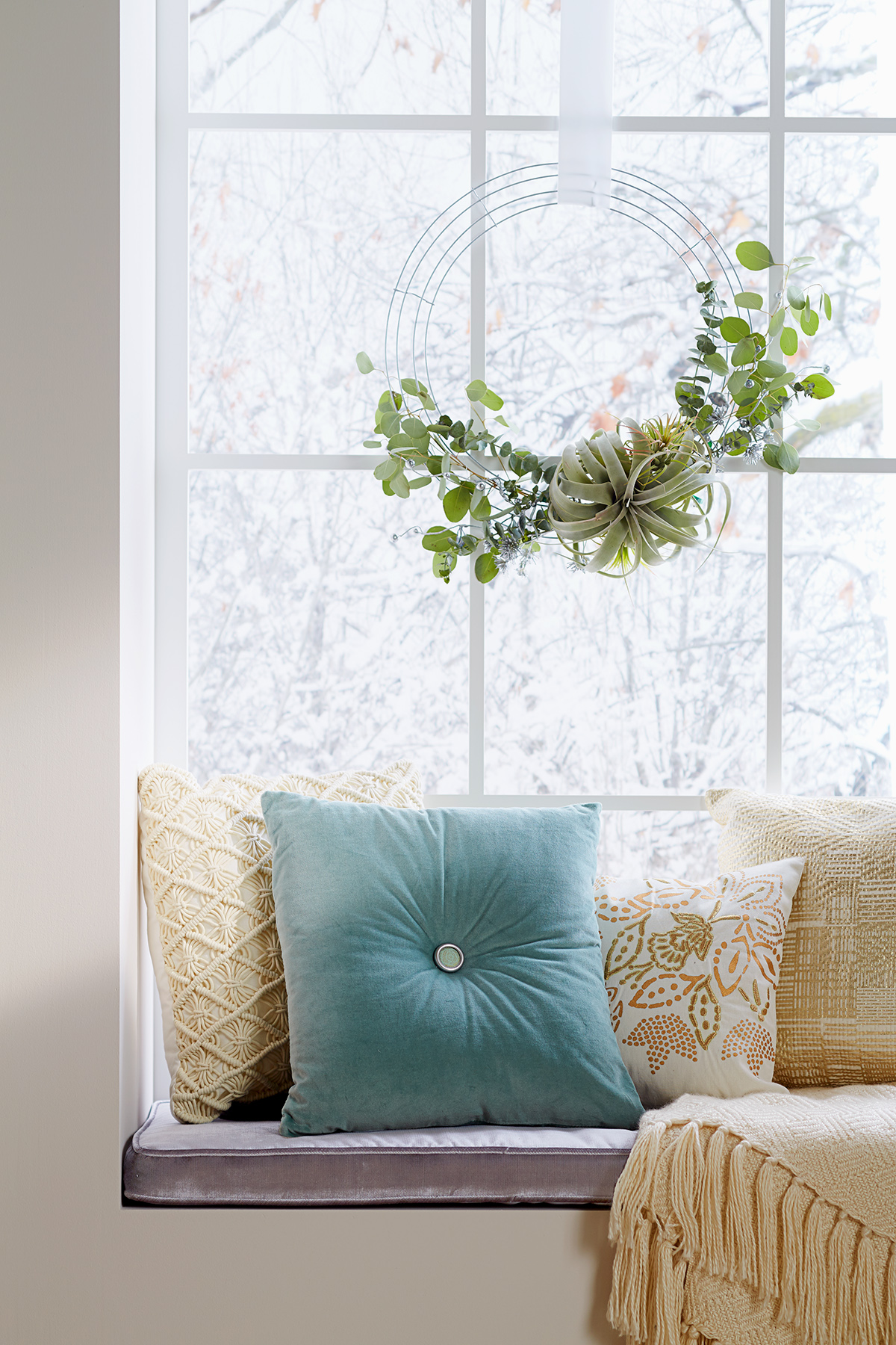 air plant wreath hung above window seat