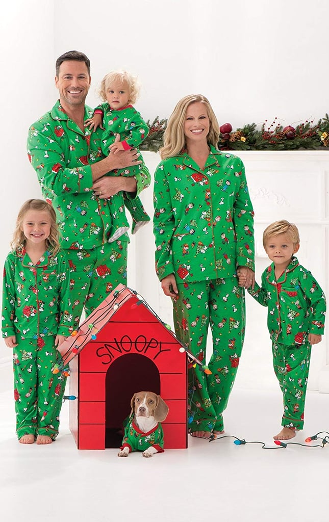 Family wearing matching green pajamas next to a red dog house