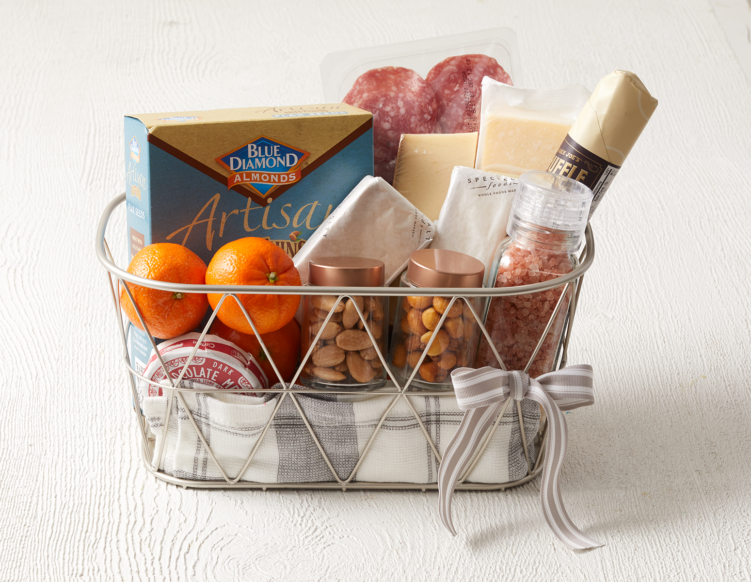 Hostess gift for foodies including a metal gift basket with tea towel, salt, almonds in canisters, boxed crackers, cheese, charcuterie, and clementines.