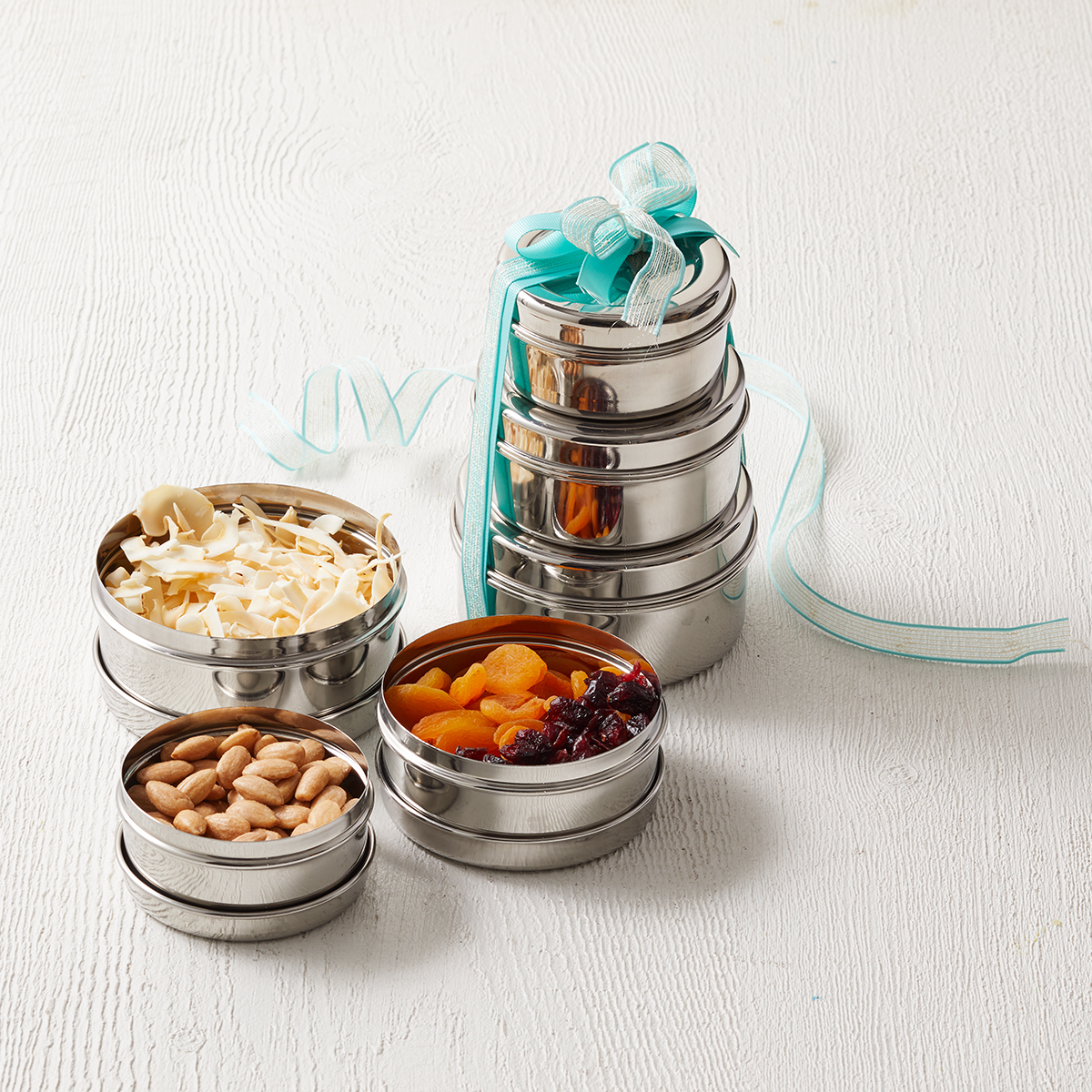 three open metal snack containers next to stack with blue ribbon