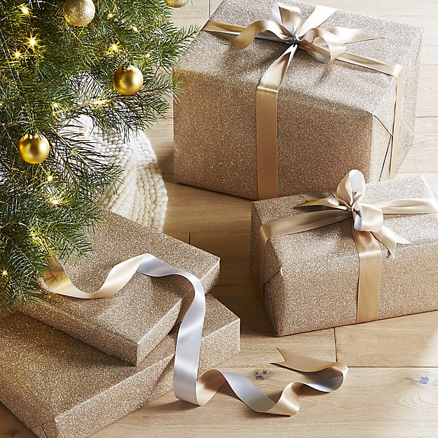 Stack of gifts wrapped in gold paper with gold ribbon