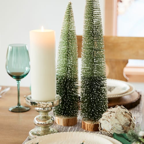 two green bottle brush christmas trees on a set table next to a white pillar candle