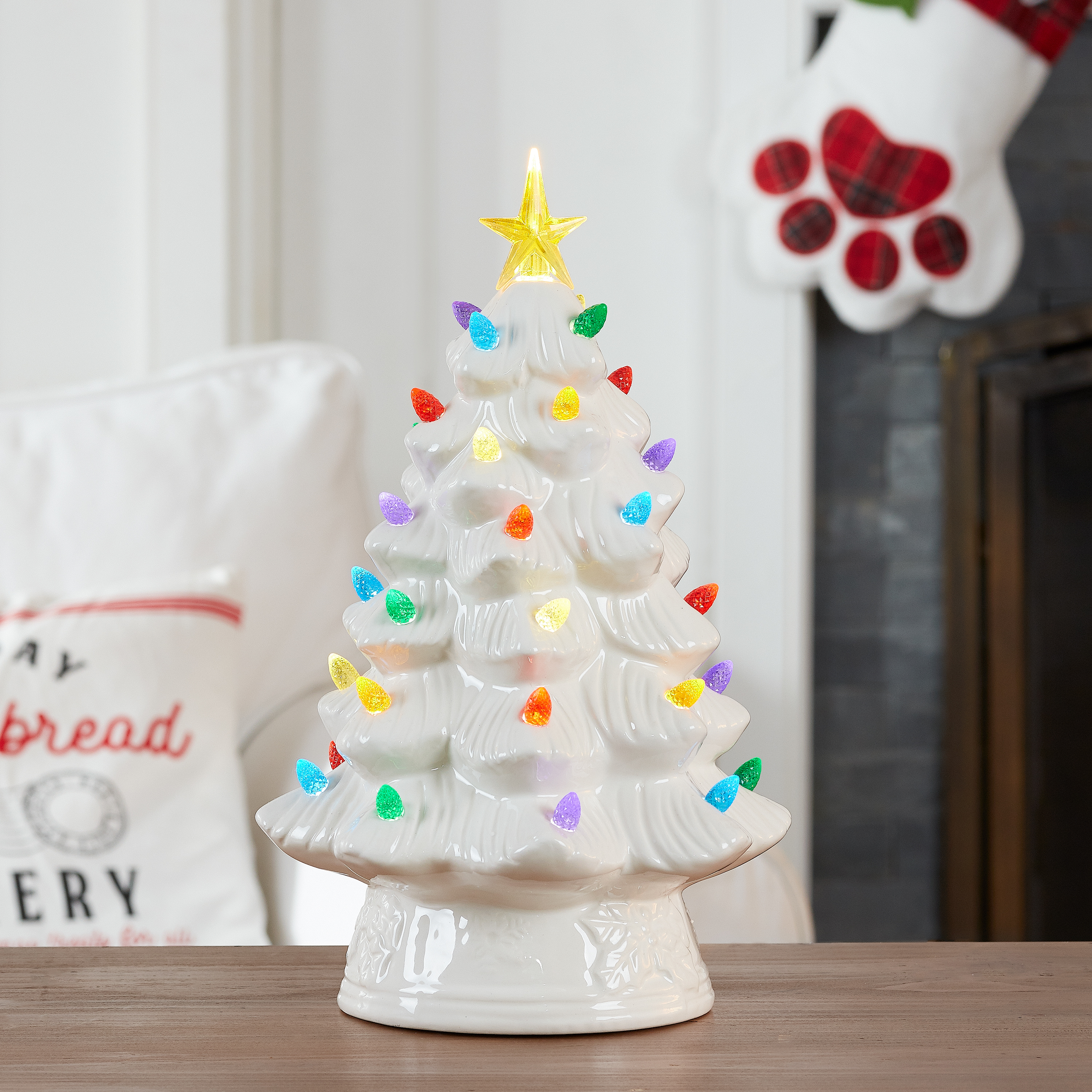 white ceramic christmas tree on a table in front of a fireplace mantel