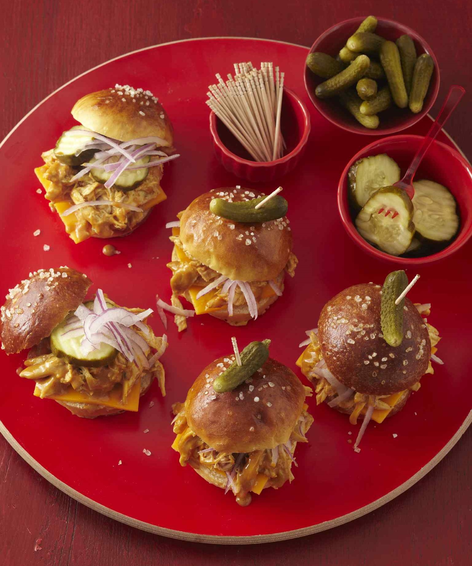 Red platter of chicken slider sandwiches topped with pickles