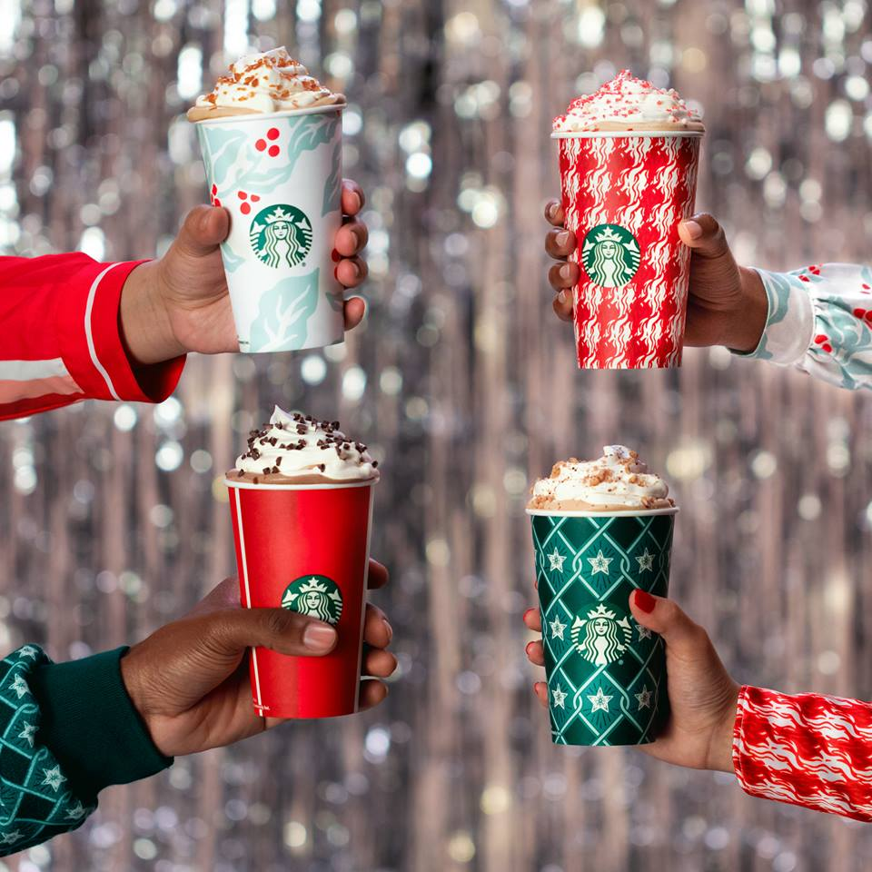 Four hands holding Starbucks holiday drinks