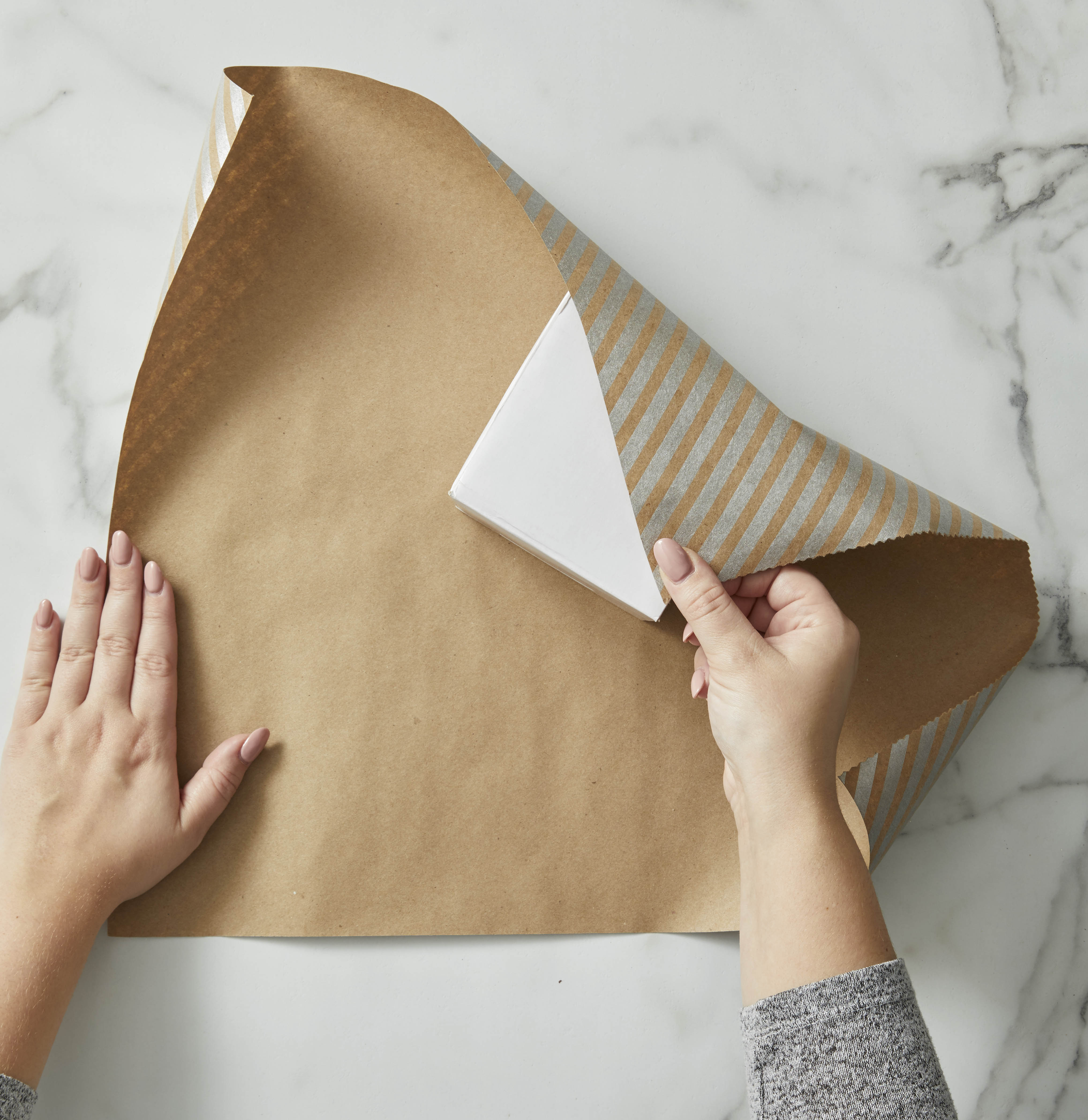 Gift wrapping folding brown paper over a box