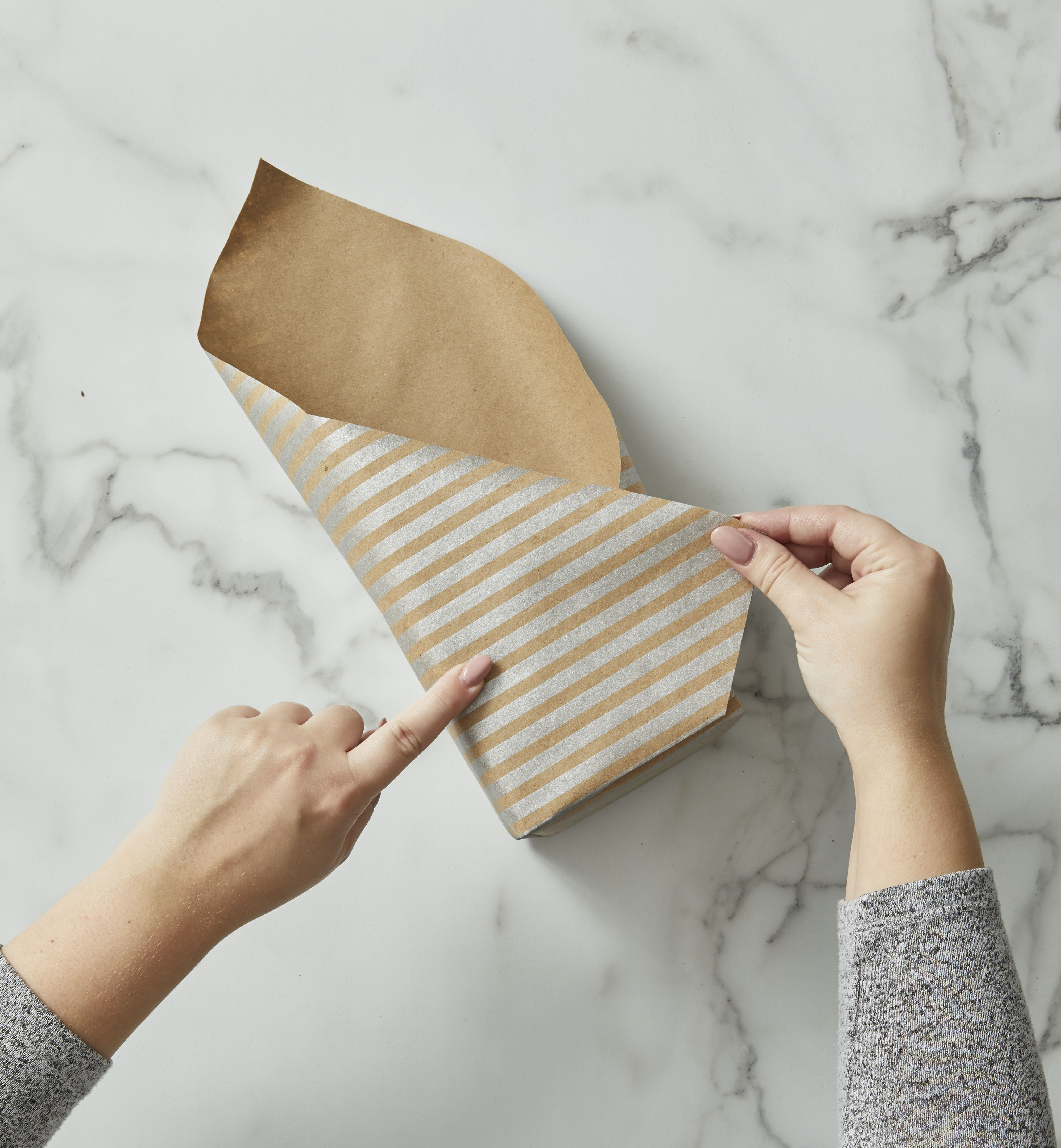 Wrapping brown striped kraft paper up and over a square box