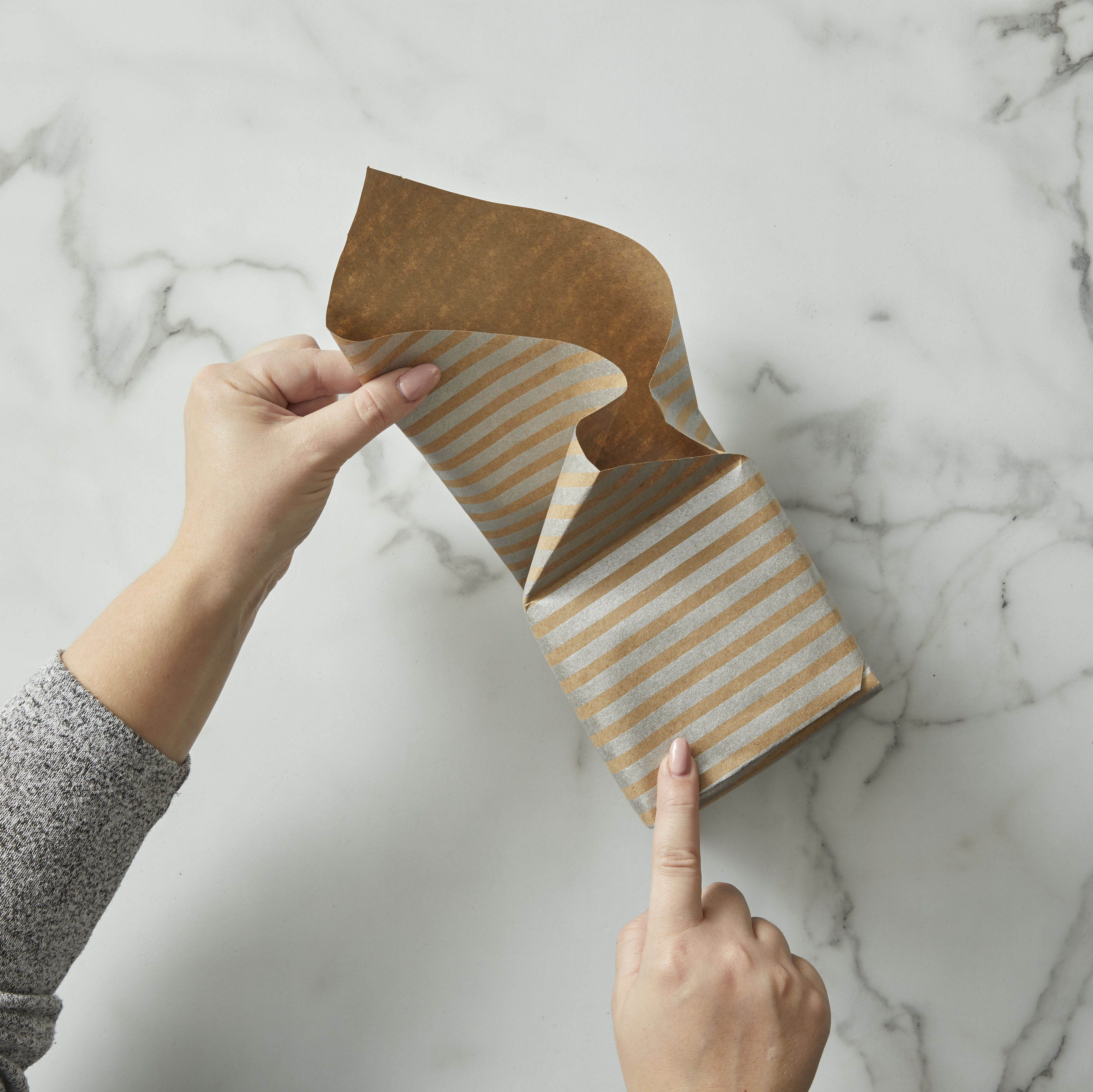 Wrapping striped wrapping paper over a square box