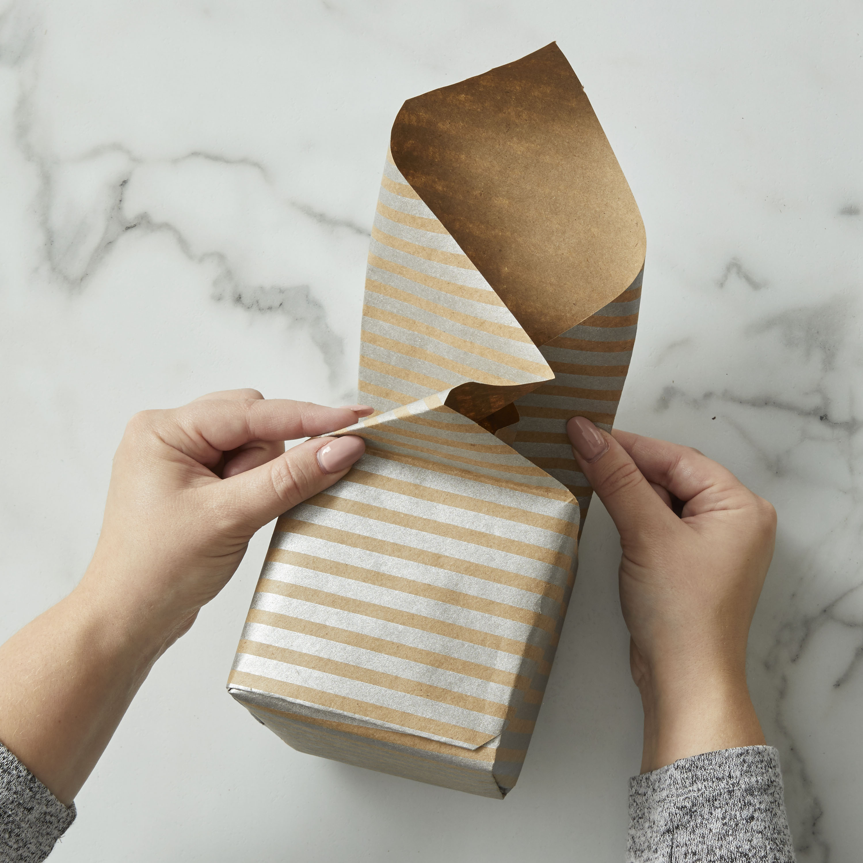 Finishing a gift wrapped in brown and silver paper