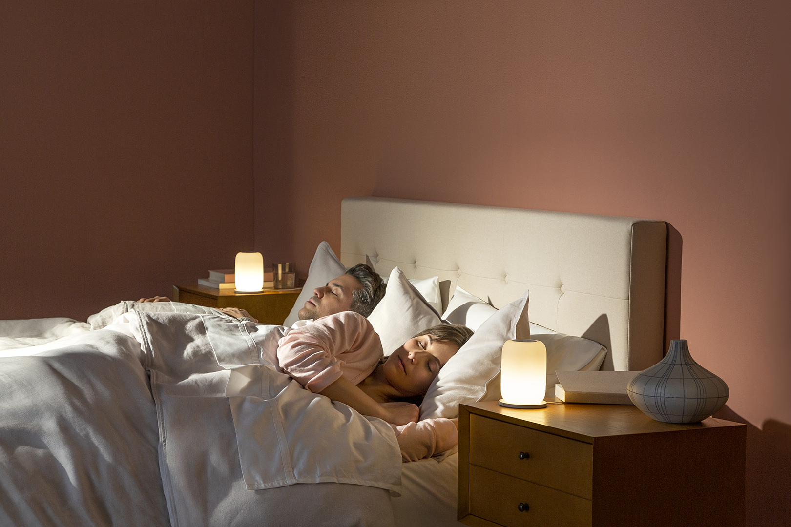 Man and woman sleeping in bed with white bedding, terra-cotta colored walls, with Casper Glow lights on wood bedside tables