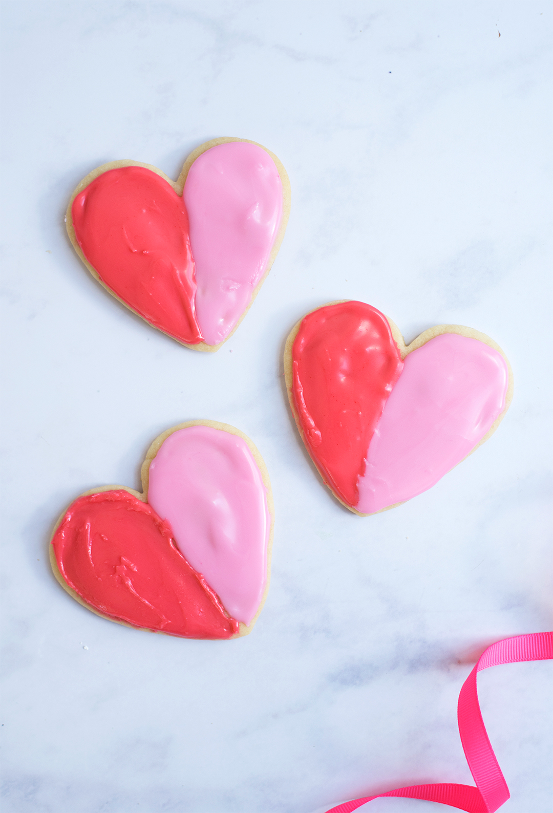 completed heart shaped cookies with red and pink frosting