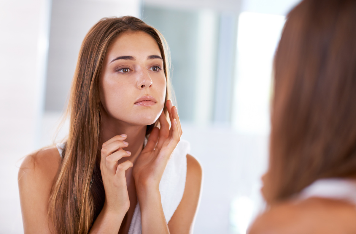 woman touching dry skin on face