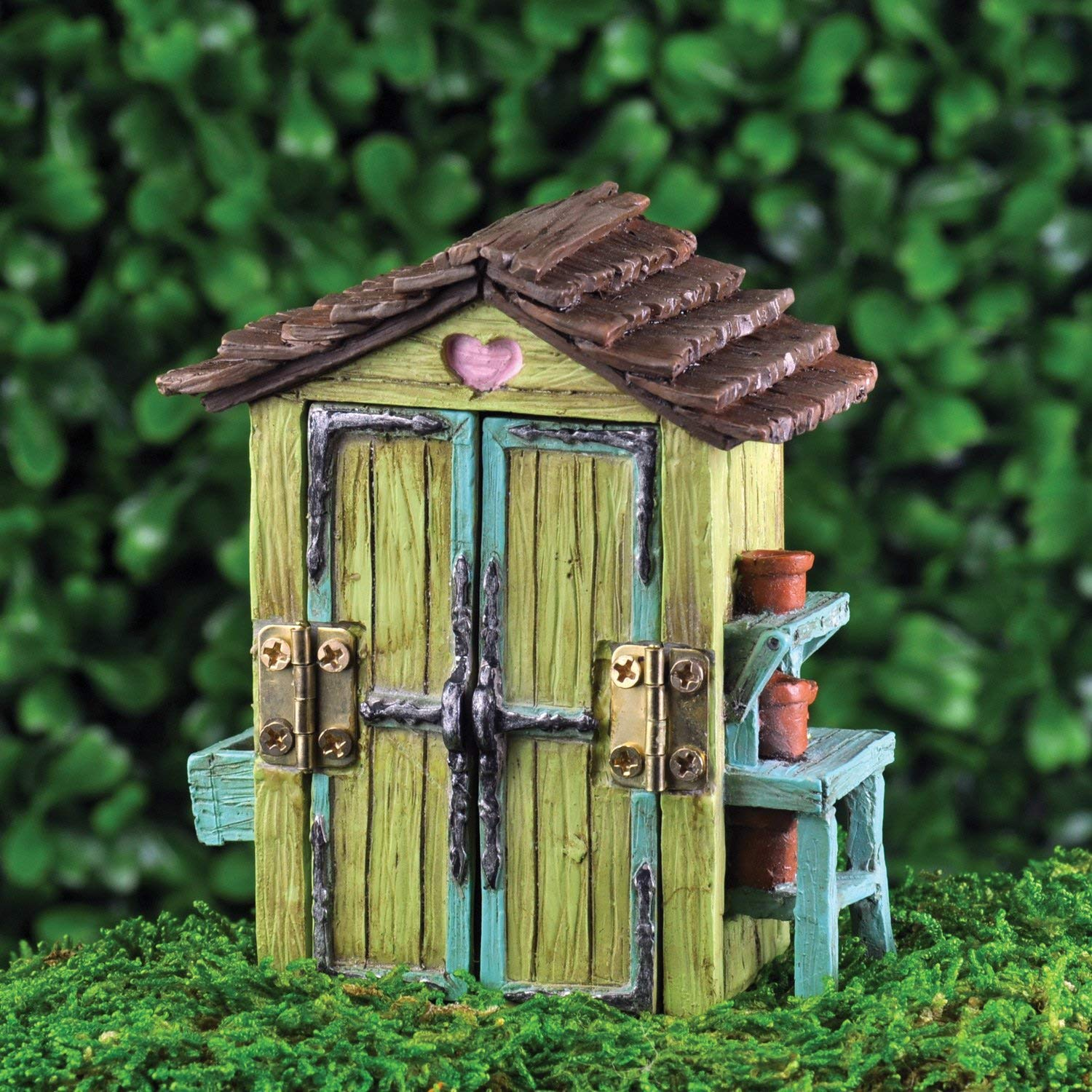 Miniature green garden shed with a blue potting bench, brown roof, and hinges that open the doors