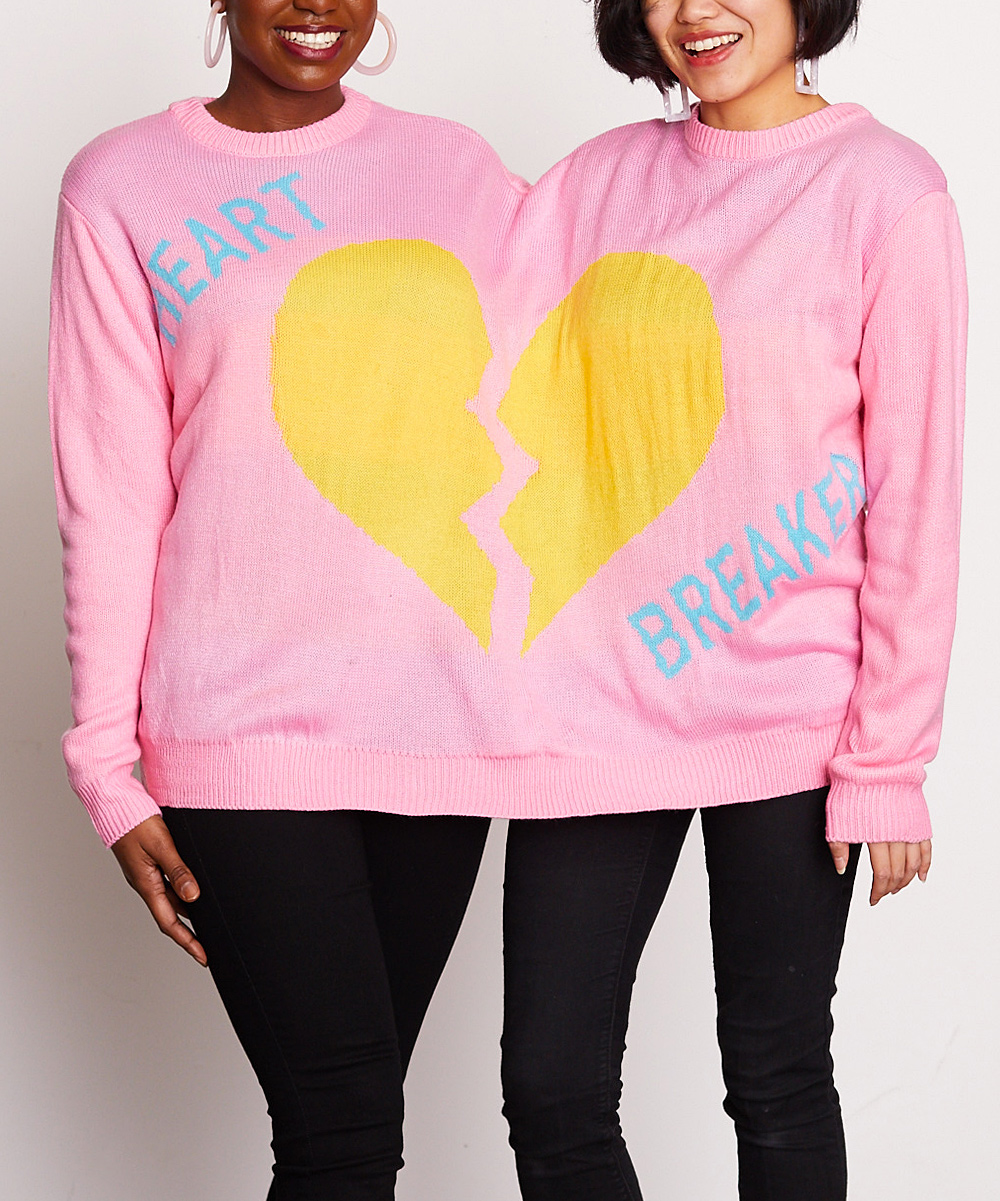 Two women wearing a pink double headed sweater with a yellow heart on it