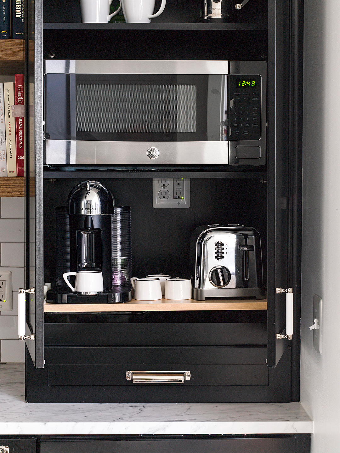 small appliances hidden in black cabinet