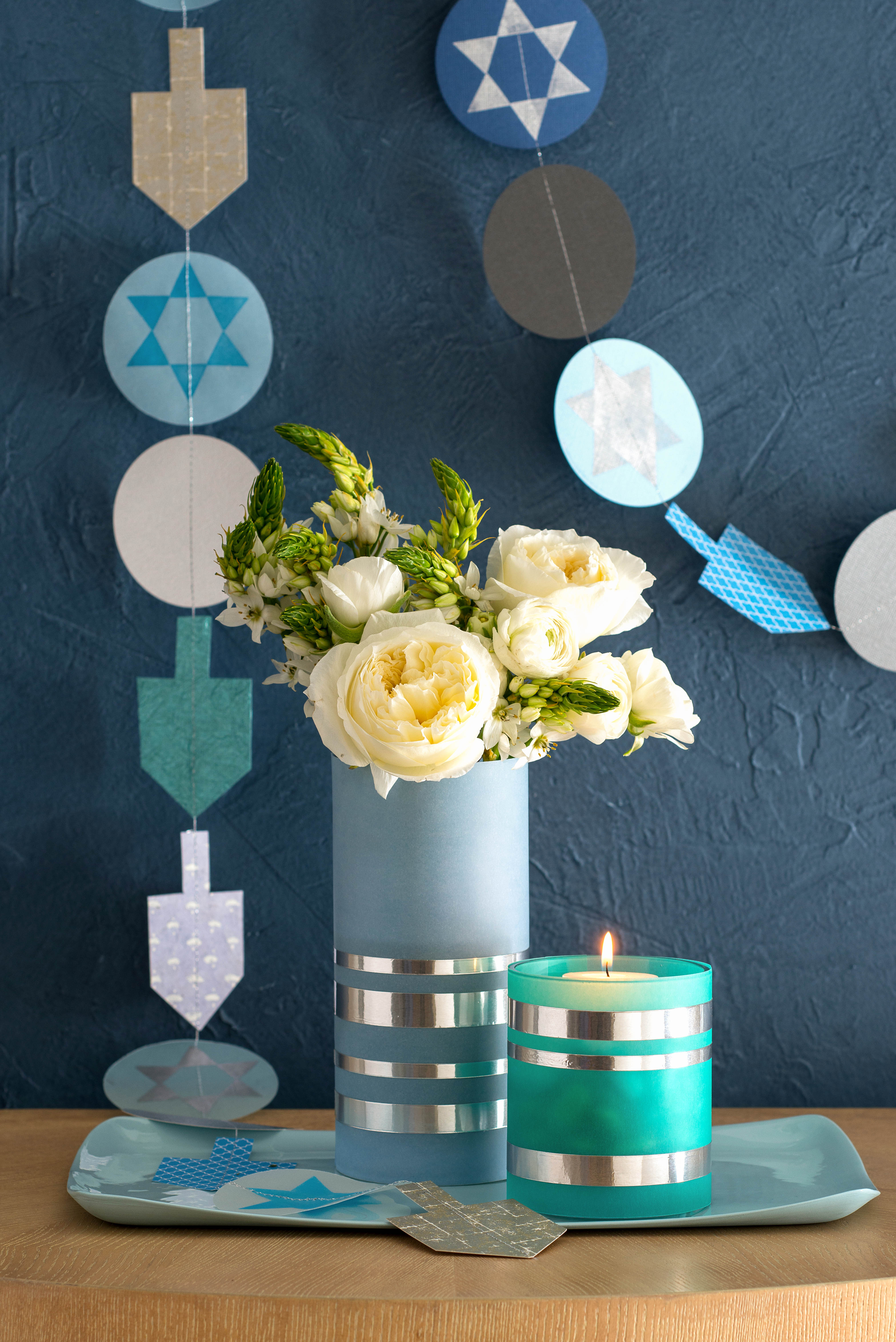 blue hanukkah decor with white flower and candle