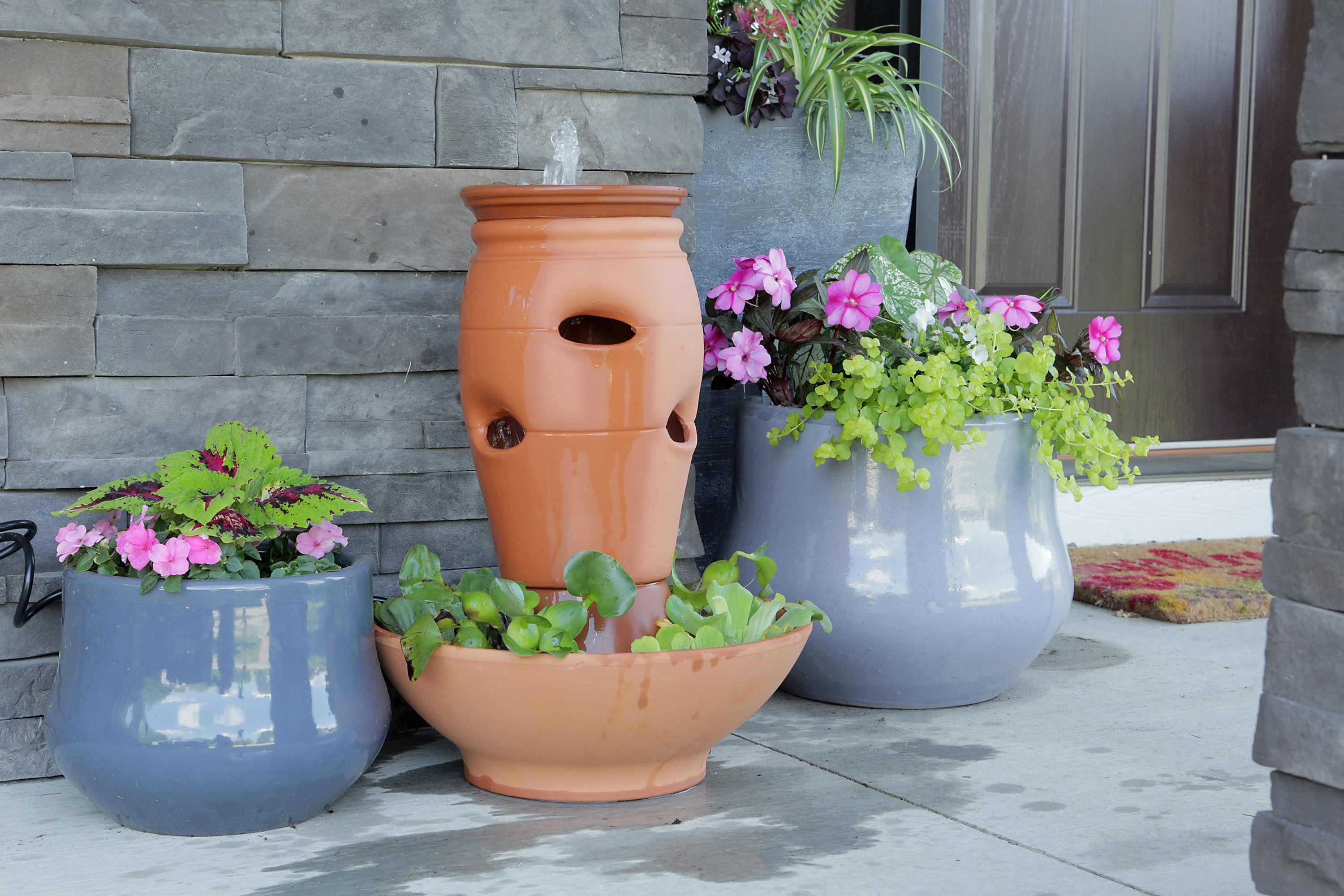 terra-cotta fountain front porch among potted plants