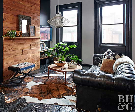 living room with leather couch and cow hide rug