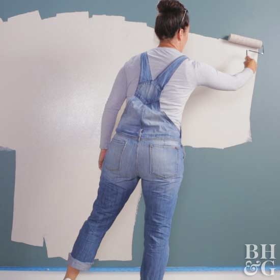 woman painting teal wall with neutral color