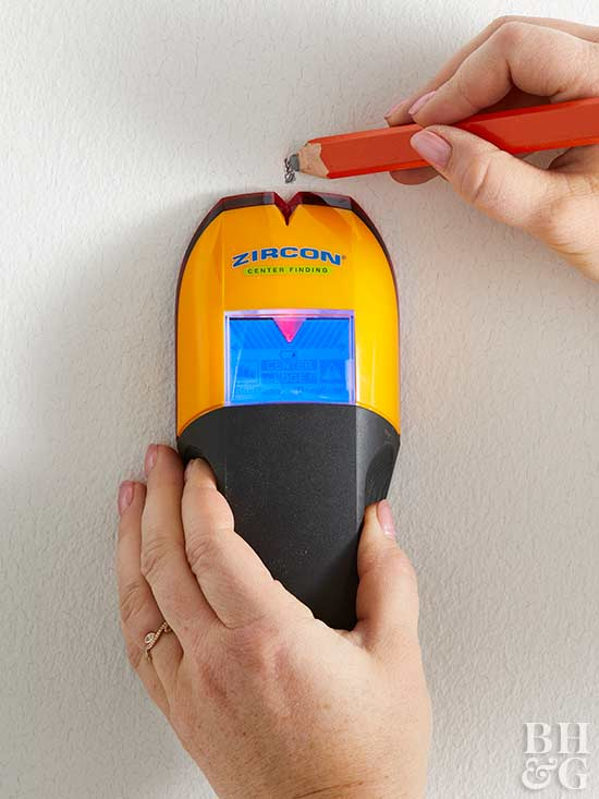 using stud finder and marking wall with pencil