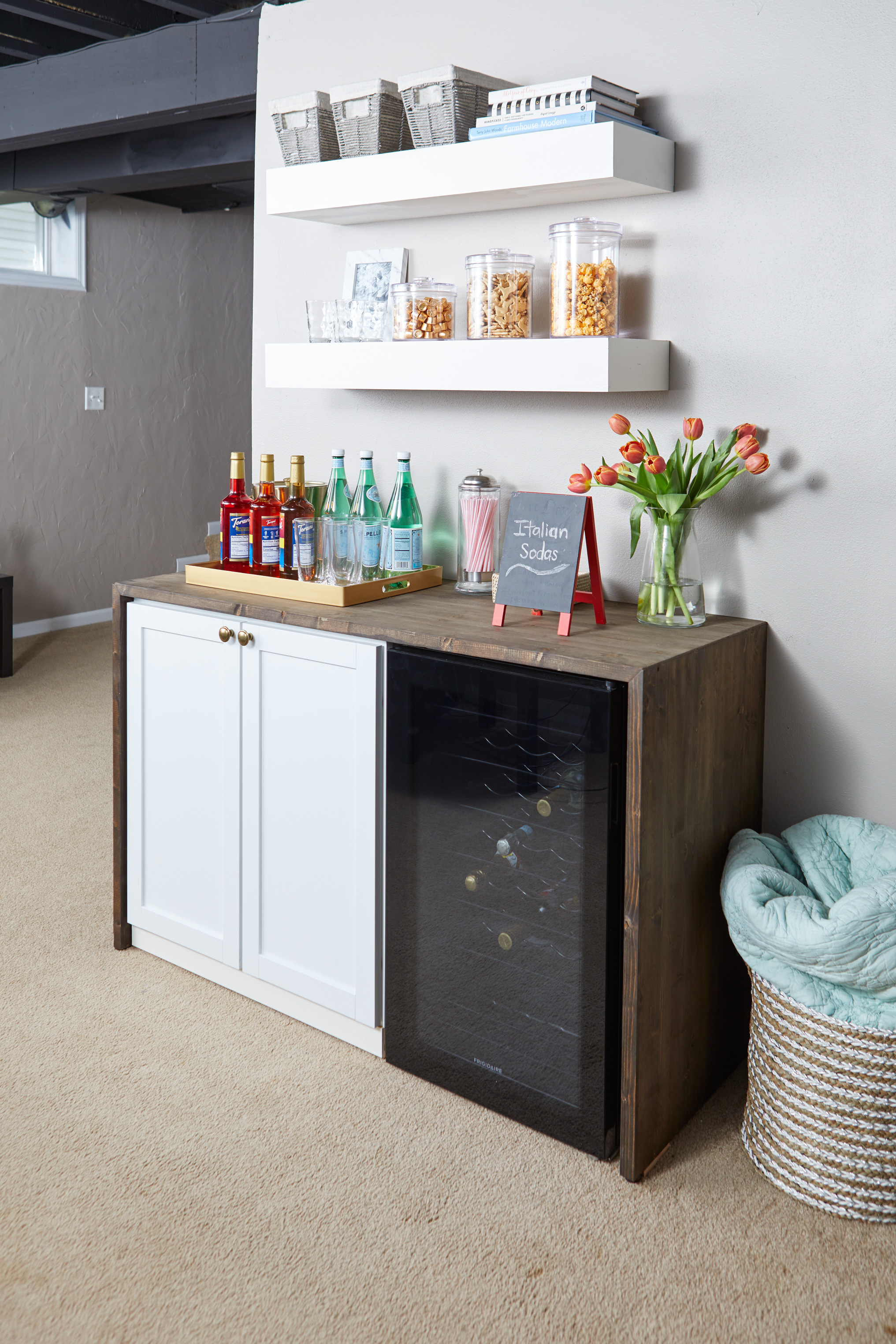 wood bar with white cabinet refrigerator and shelves basement