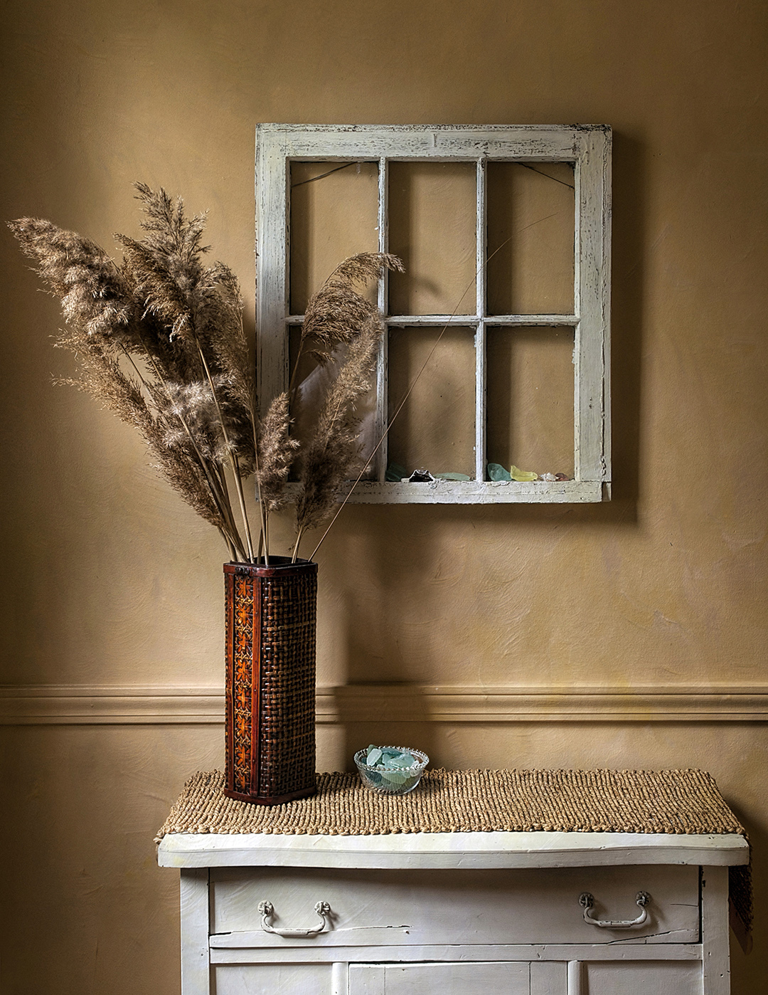 Brick-colored vase filled with ivory pampas grass on top of a white side table, antique window hanging on wall behind