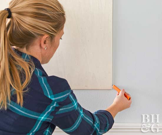 woman marking wall with pencil