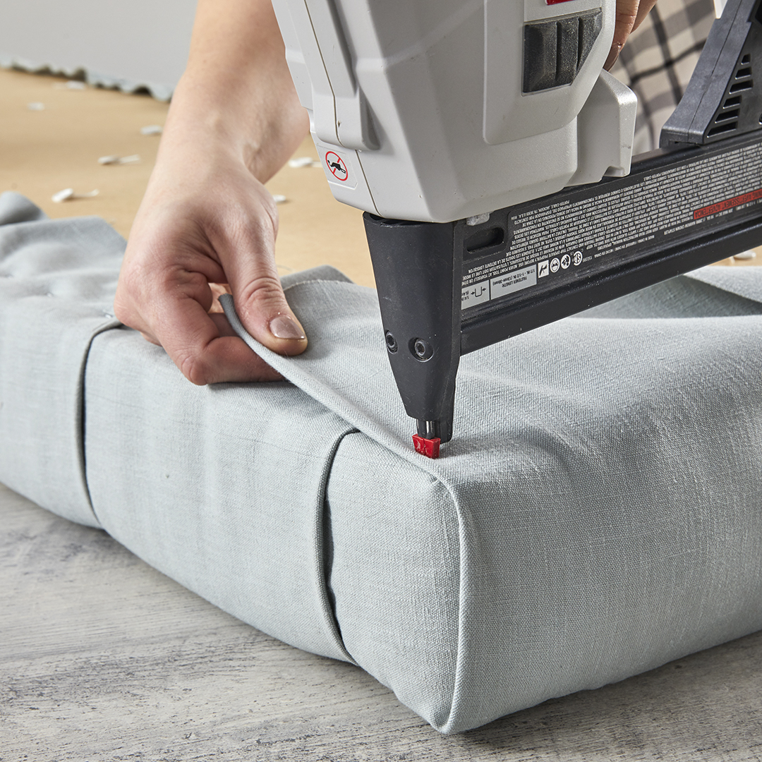 stapling excess fabric from corner of tufted bench