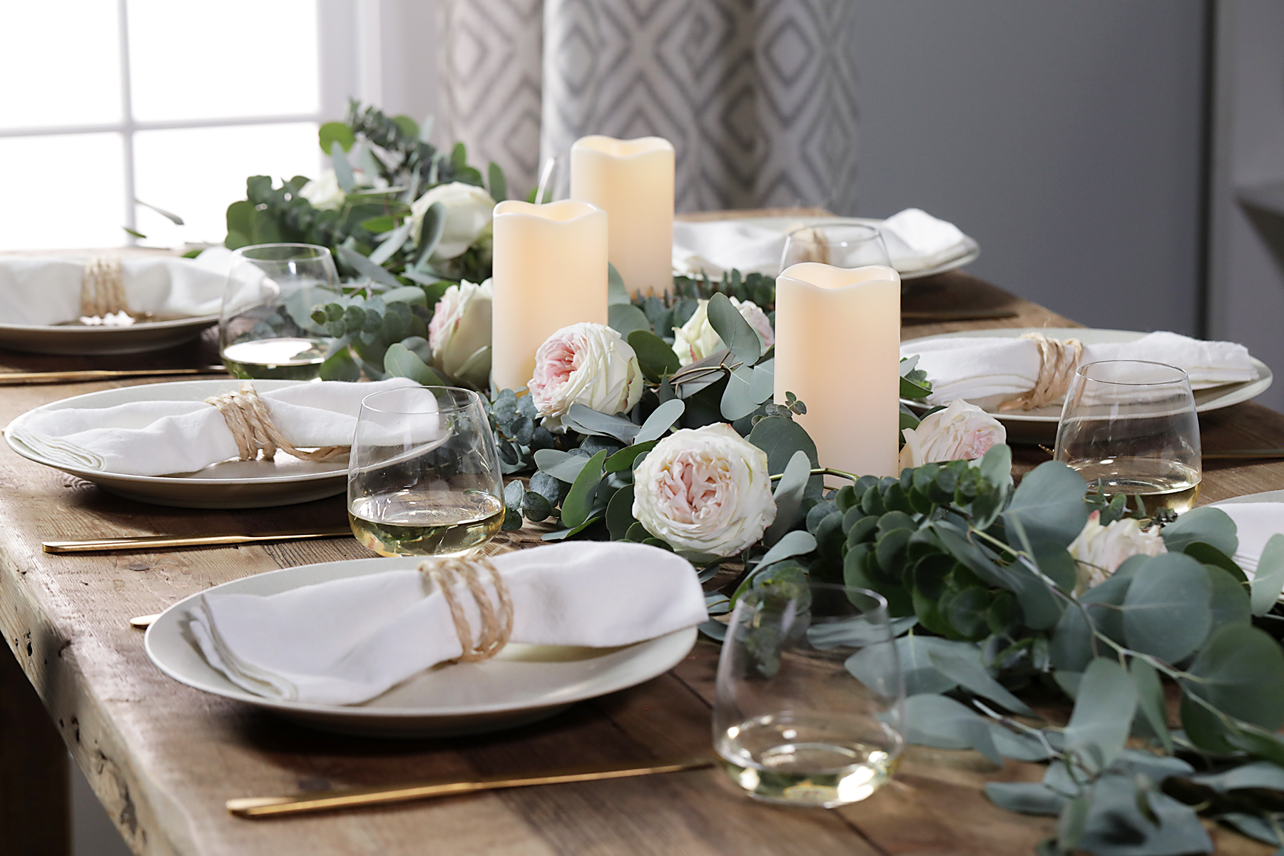 table decor with eucalyptus garland white candles place settings