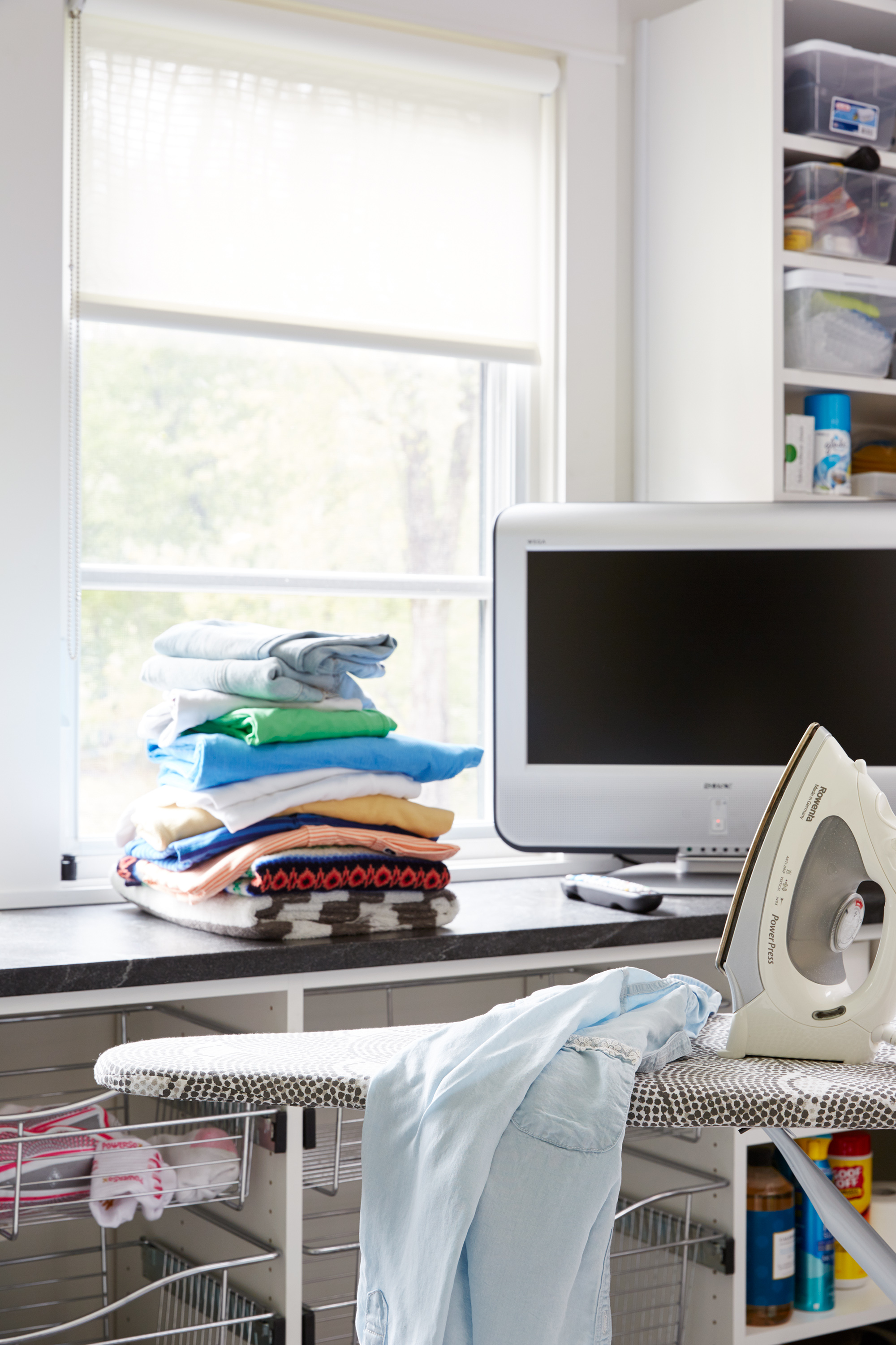 Juliano laundry room with ironing board and tv