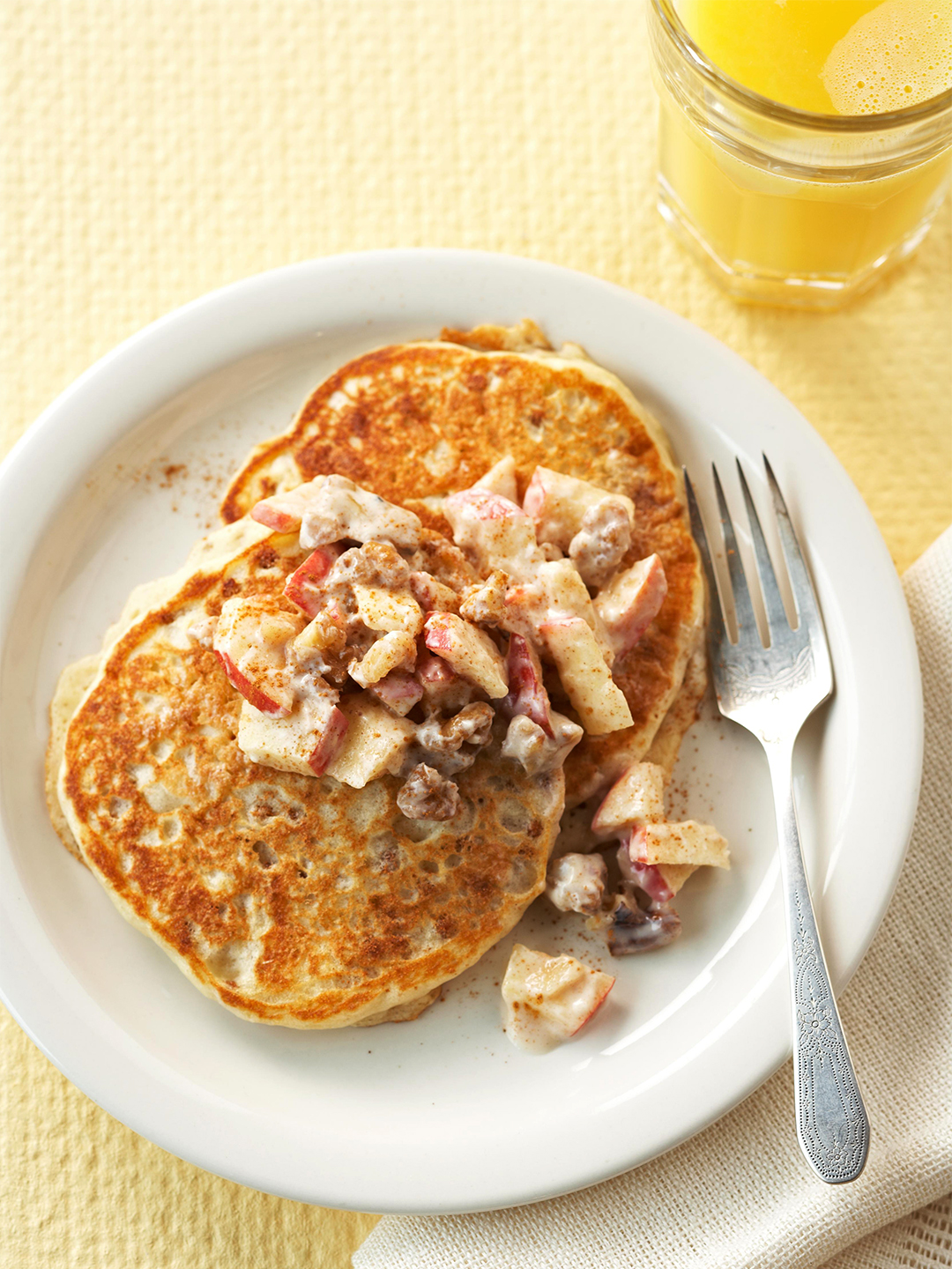 Buttermilk Bran Cakes with Apple-Walnut Topping on plate with glass of orange juice