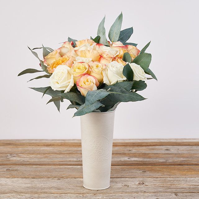 peach roses and greenery in a white vase on a wood table