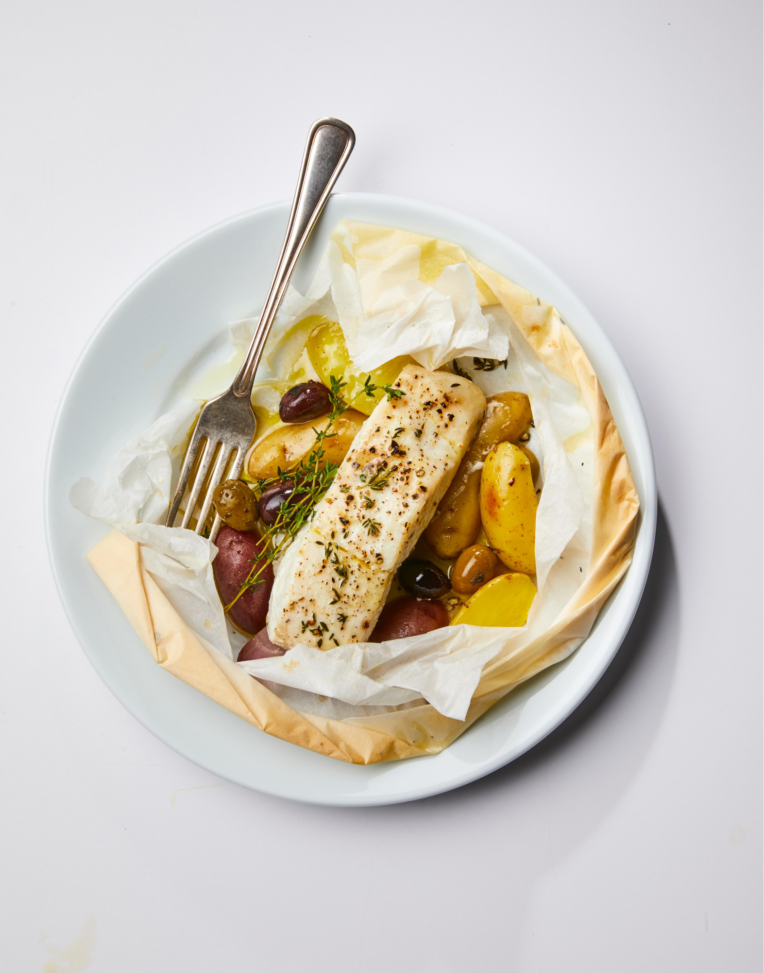 Parchment-Baked Halibut with Thyme and Olives on a plate with fork