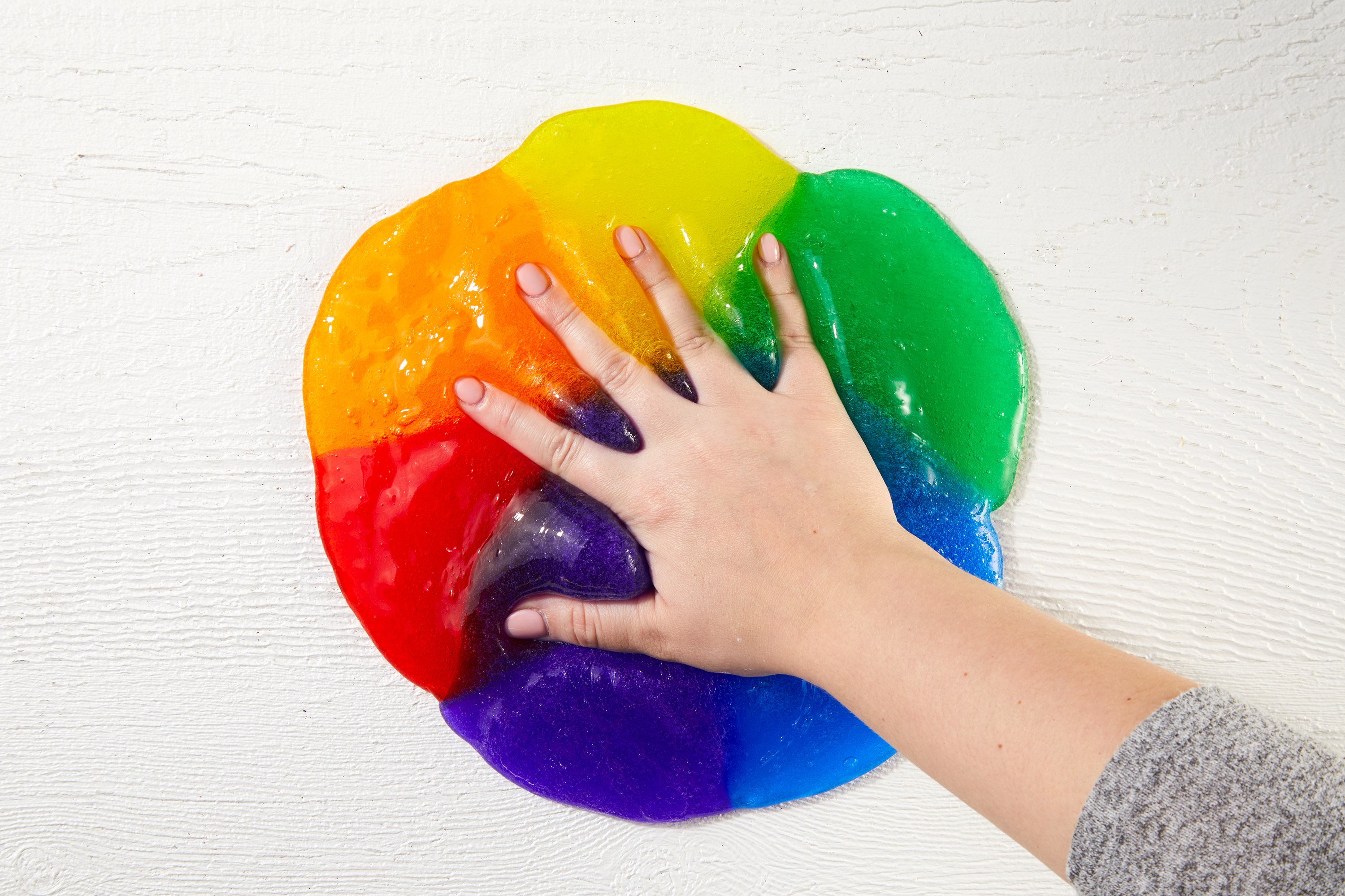 making hand impression in rainbow slime