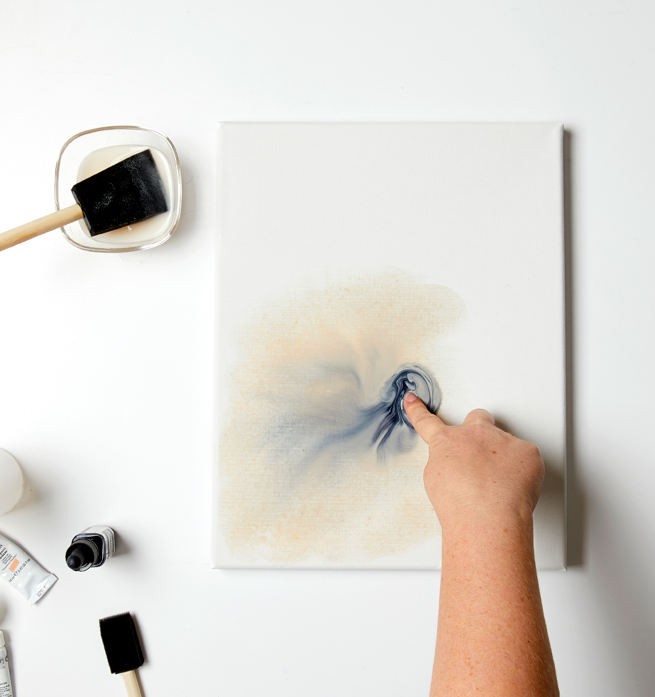 smearing watercolor on canvas with finger