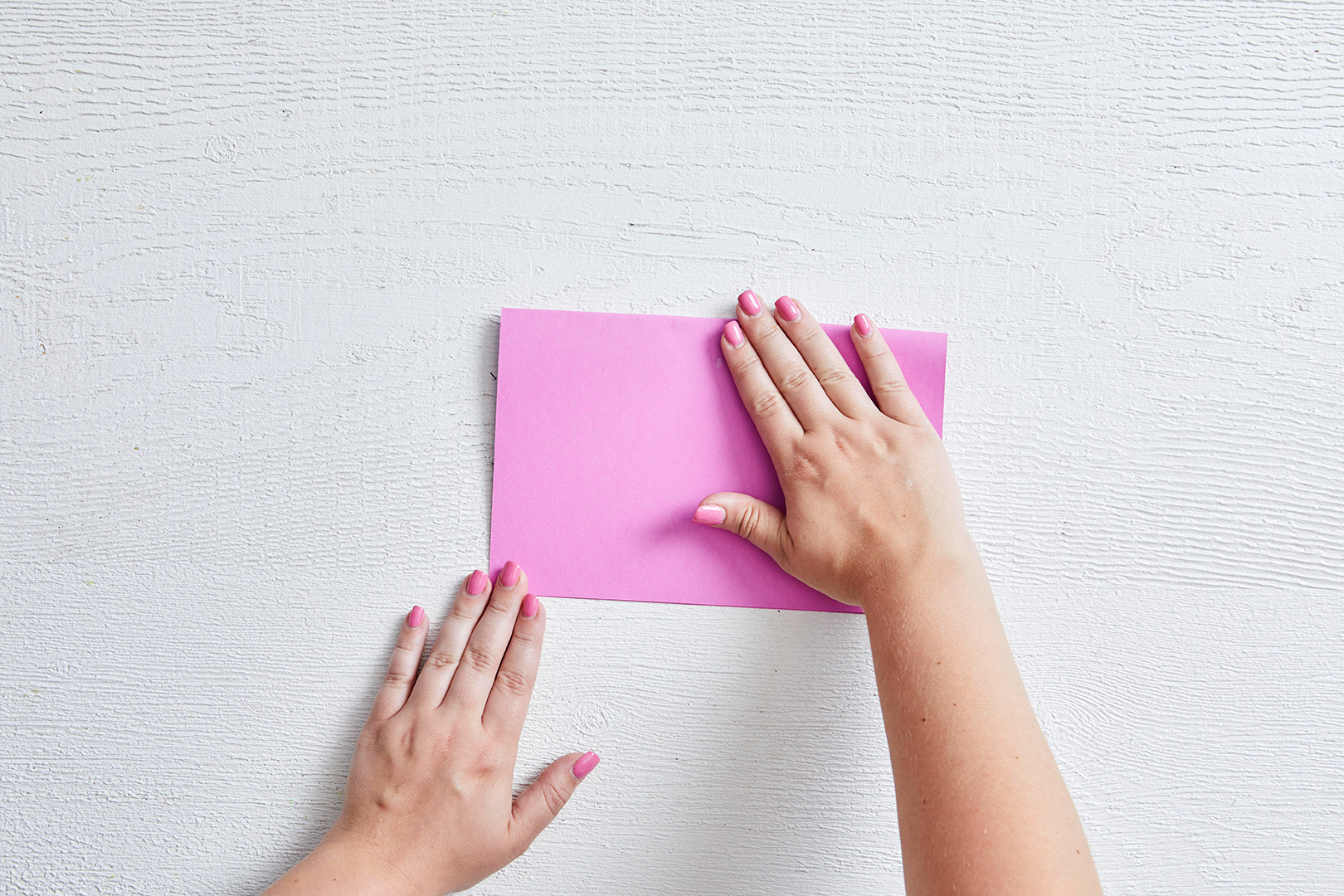 folding pink sheet of paper in half vertically woman's hands