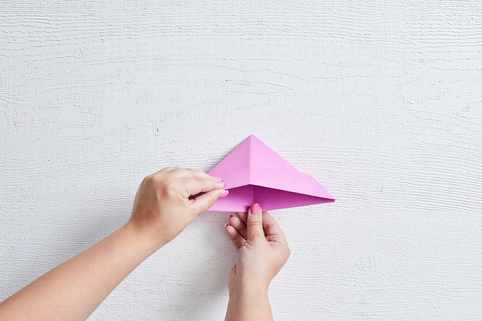 opening folded paper boat to reveal inside woman's hands